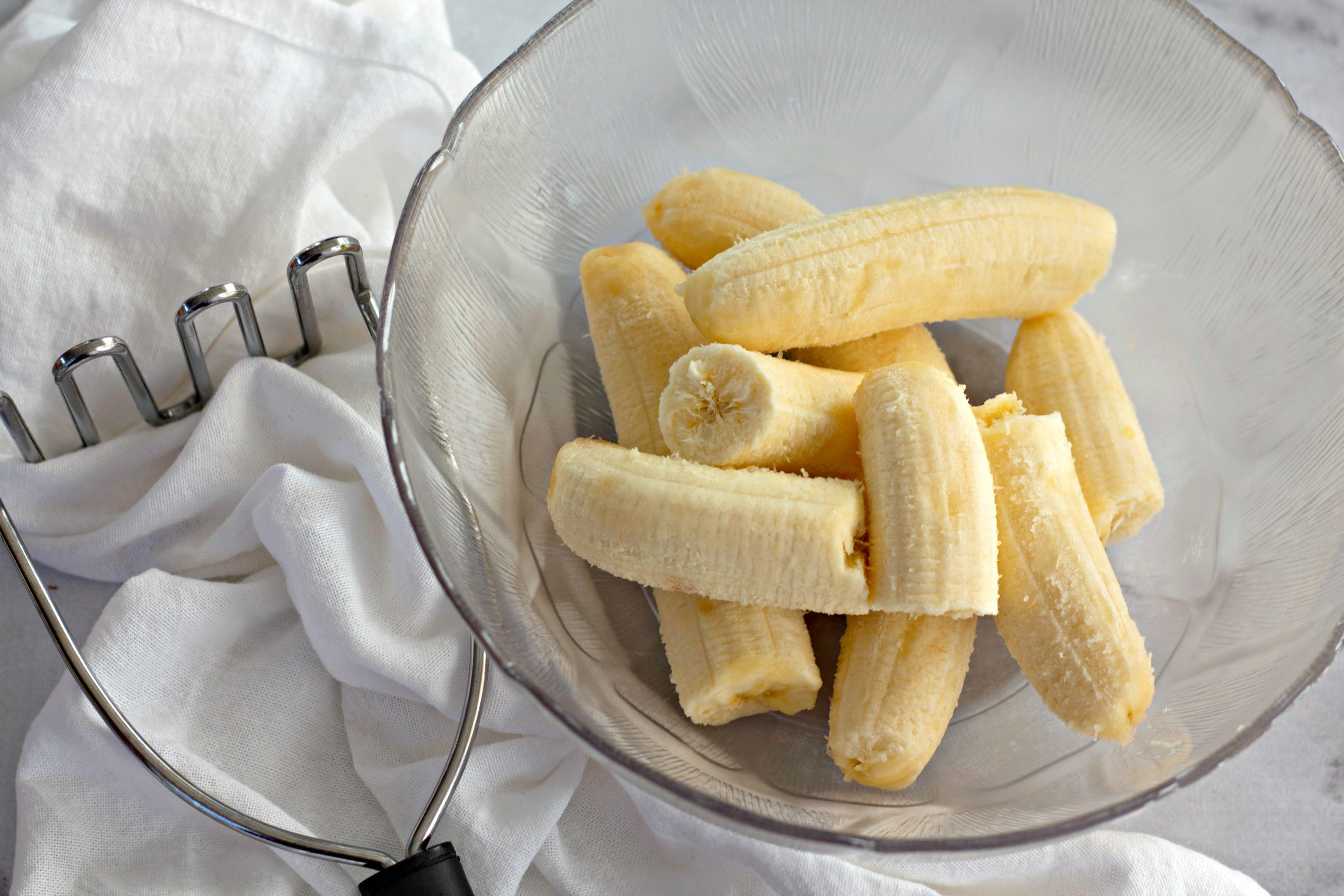 an image of a bowl of bananas and a potato masher