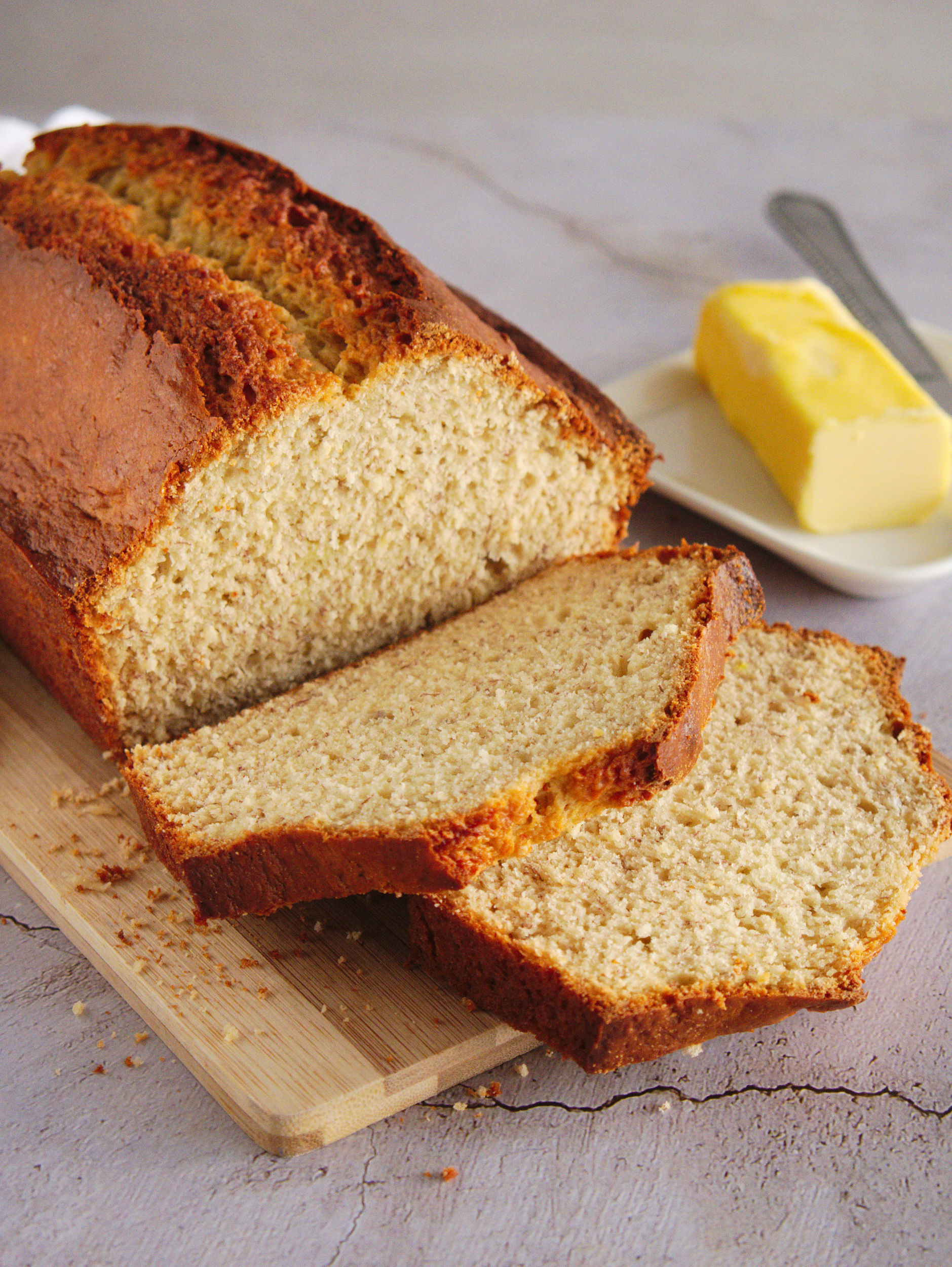 a loaf of banana bread with a few slices sliced off and a stick of butter beside it
