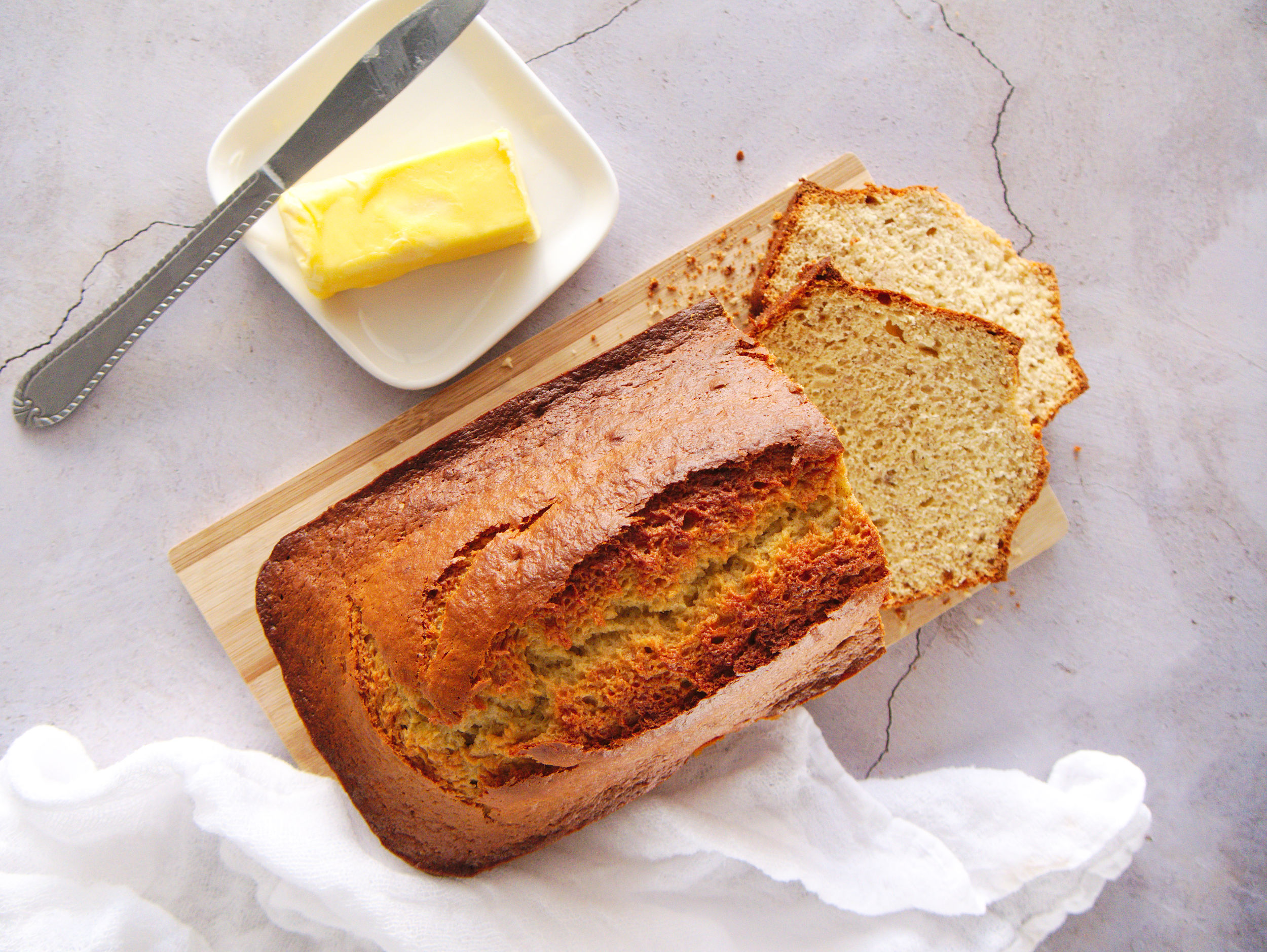 an image of a loaf of banana bread, from above, with a couple slices sliced off, and a side of butter and a knife beside the loaf