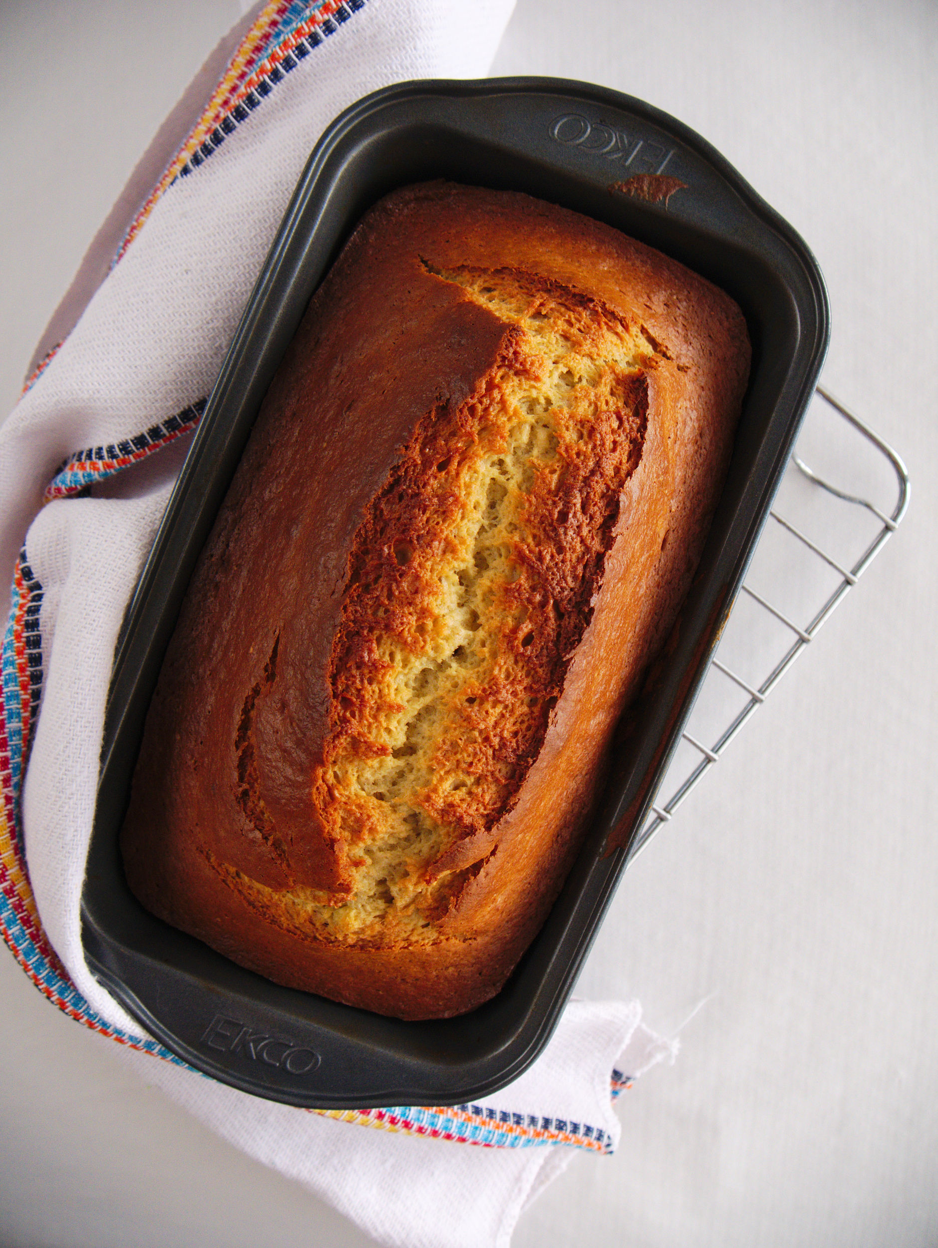 fully baked banana bread, still in the loaf pan, cooling on a rack