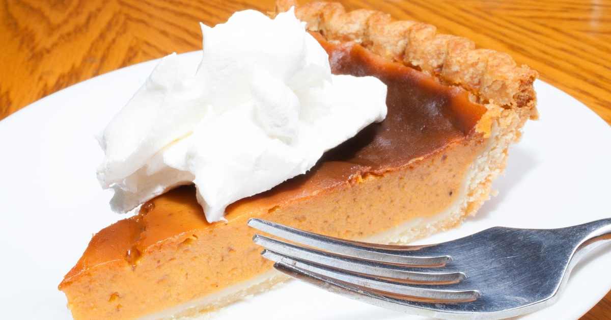 Fork and sweet potato pie with whipped creme on a white plate