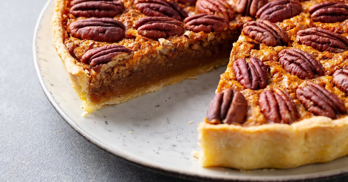 a molasses pumpkin pecan ginger pie with a slice missing