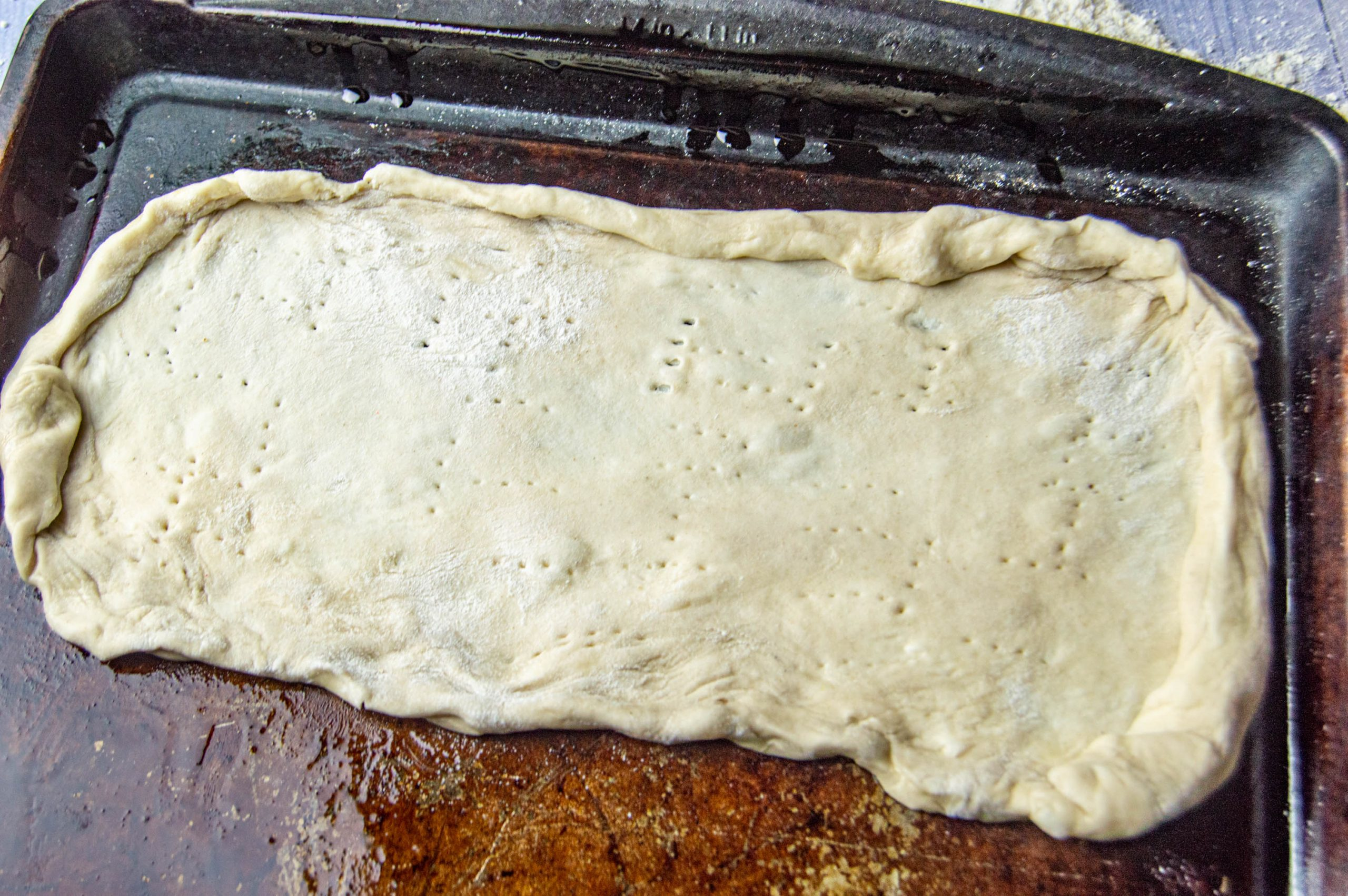 pizza dough rolled and shaped into a crust, on an oiled baking sheet, and pierced with a fork several times