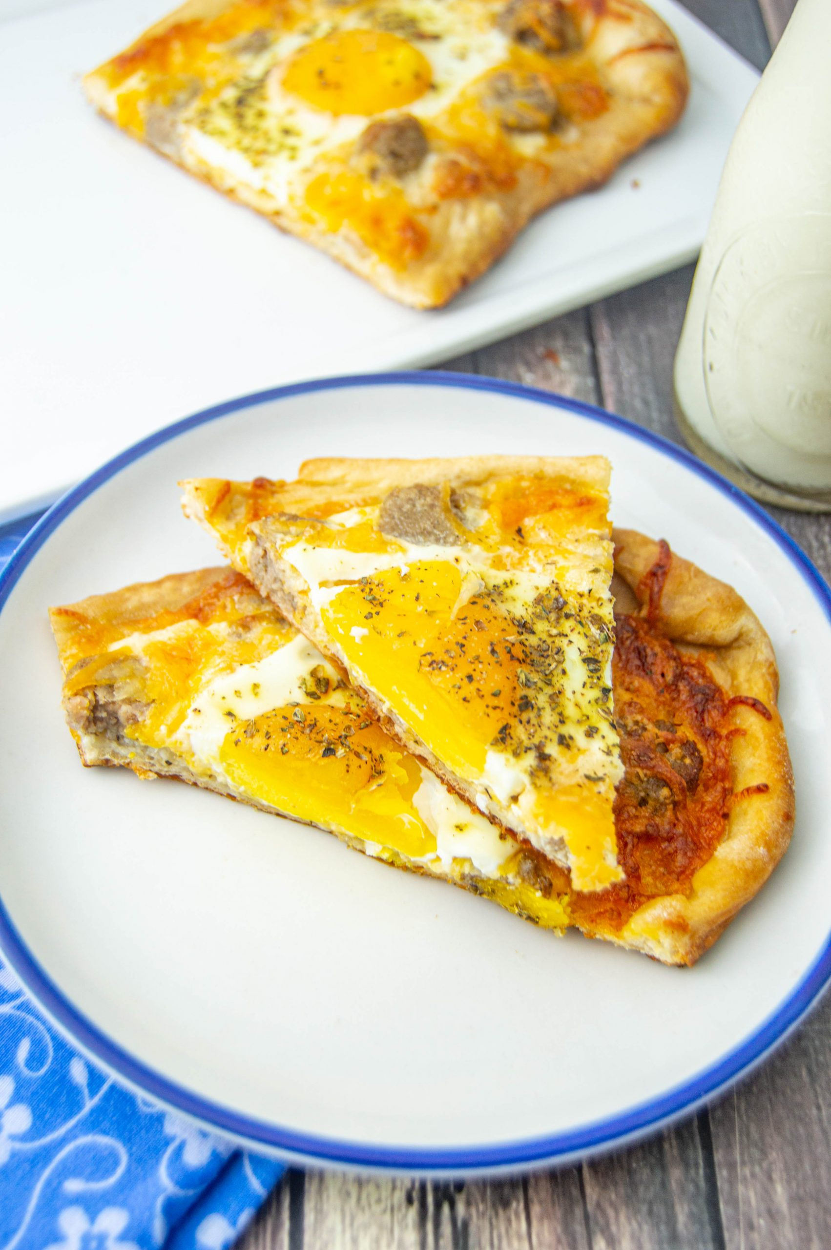 two slices of breakfast pizza stacked on a plate