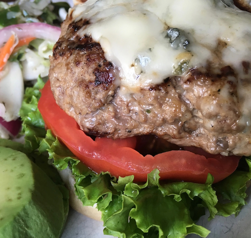 burger topped with blue cheese, tomato and lettuce, with a side salad