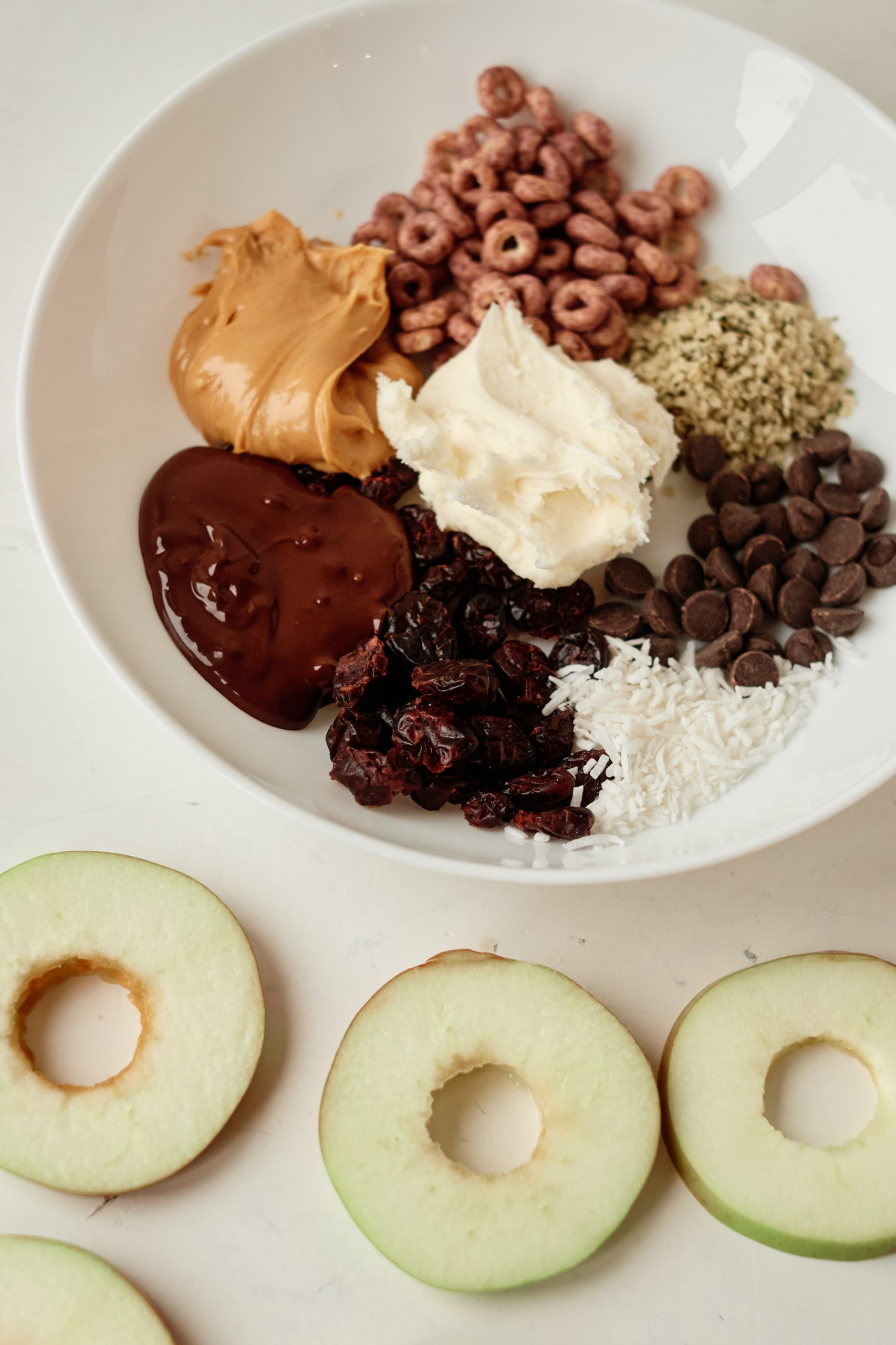 a plate full of possible toppings for apple donuts
