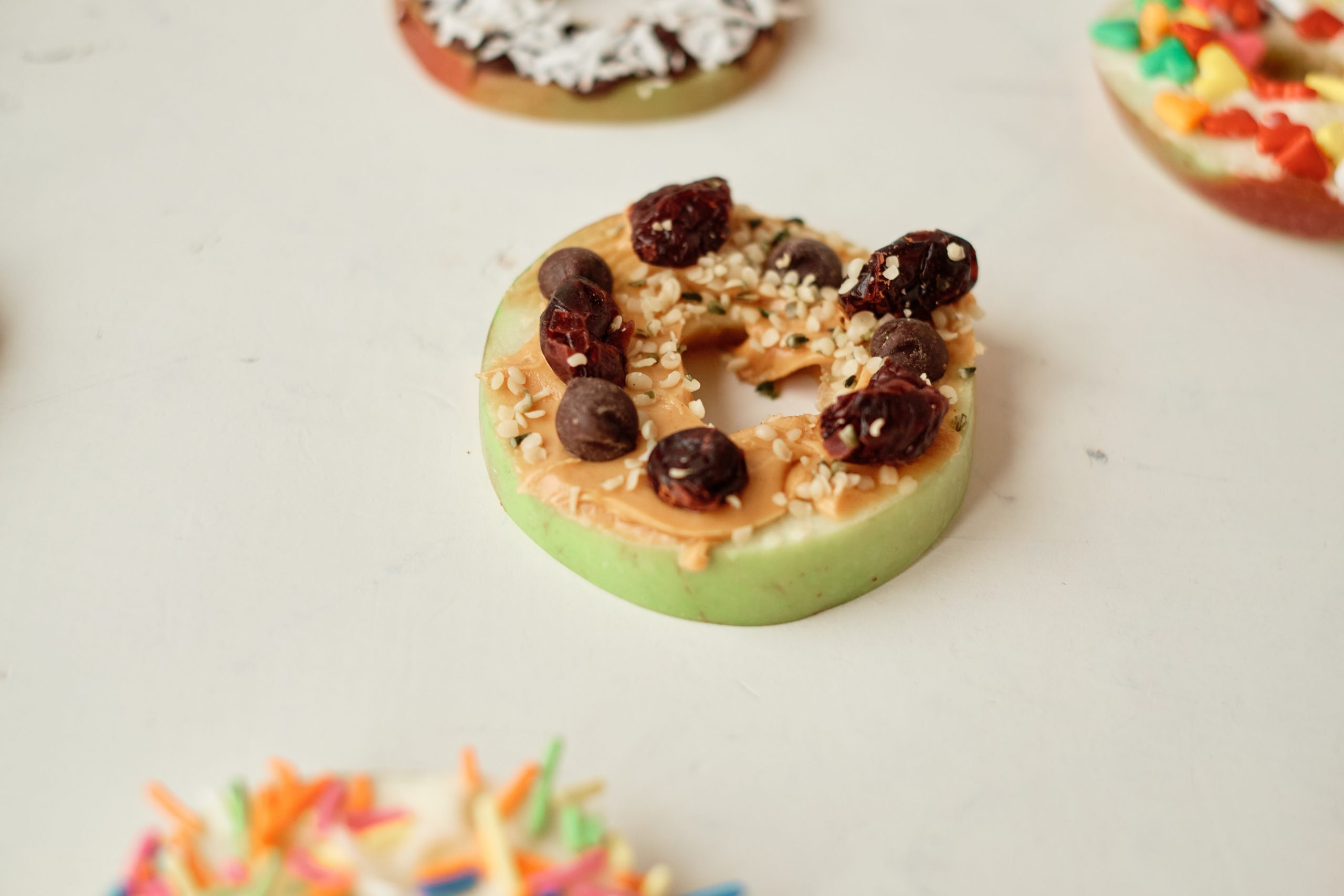an apple donut topped with peanut butter, hemp seeds, chia seeds, and craisins